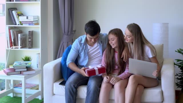 dotter ger överraskande present till far och mor förälder sitter på soffan - birthday celebration looking at phone children bildbanksvideor och videomaterial från bakom kulisserna