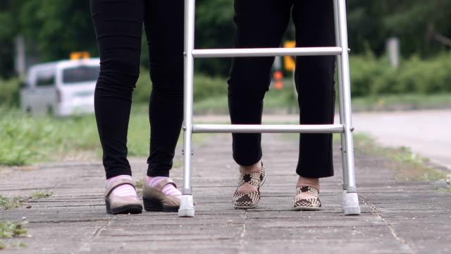 Daughter take care elderly woman walking on street video