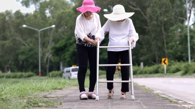 Hija cuidar anciana caminando en la calle - vídeo