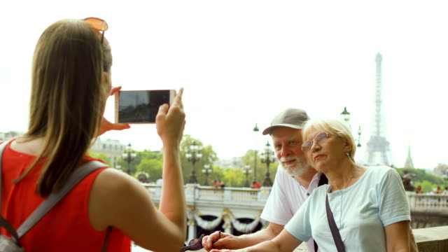 Daughter taking photo of senior parents on vacation trip in Paris. near Eiffel Tower and river Seine video
