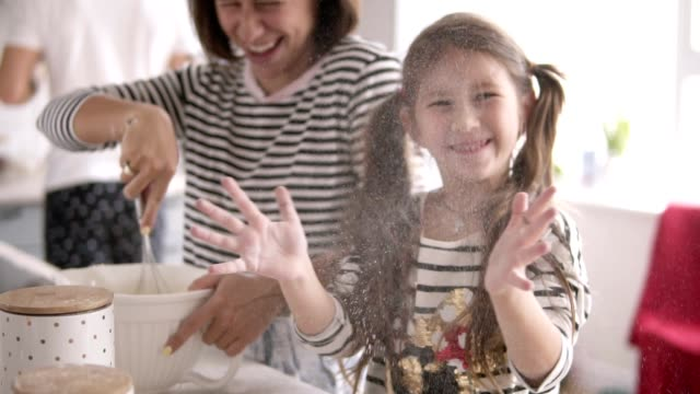 daughter throws flour and mother is kneading the dough on the kitchen - pancake video stock e b–roll