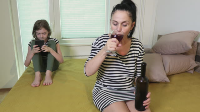 Daughter using smartphone near mother with bottle of wine - vídeo
