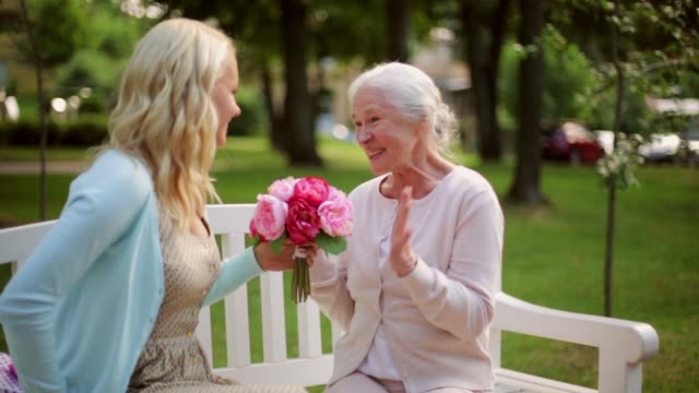daughter with flowers and gift for senior mother family, holidays and people concept - happy smiling young daughter giving flowers and present to her senior mother sitting on park bench mothers day stock videos & royalty-free footage