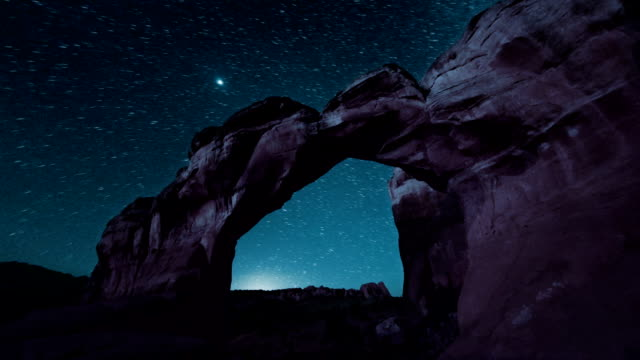 dawn breaking over rock arches video