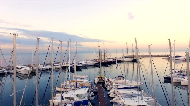 vídeos de stock e filmes b-roll de dawn in the greek marina, athens. aero video shooting. a lot of different yachts, catamarans moored to piers. in the background is the landscape of sea , blue sky. summer clear morning, calm mediterranean sea - ibiza