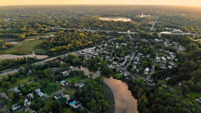 vídeos de stock, filmes e b-roll de alvorecer na área de dormir de uma cidade pequena com uma floresta no fundo. vista de uma altura - sol nascente horizonte drone cidade