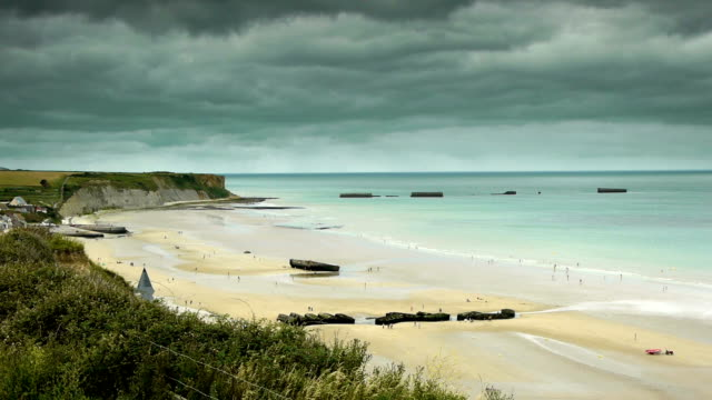 D Day beach at Arromanches, France D Day beach at Arromanches, France. A wide shot of Gold Beach at Arromanches les Bains in Normandy. The coastline and some remains of huge military concrete blocks in the water, a memorial of the invasion of Operation Overlord at World War II. normandy stock videos & royalty-free footage