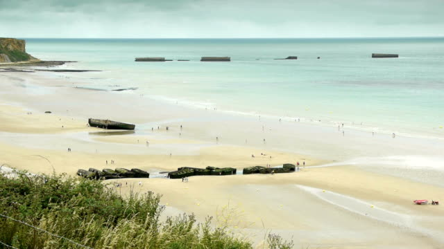 D Day beach at Arromanches les Bains, France D Day beach at Arromanches, France. A wide shot of Gold Beach at Arromanches les Bains in Normandy. The coastline and some remains of huge military concrete blocks in the water, a memorial of the invasion of Operation Overlord at World War II. normandy stock videos & royalty-free footage