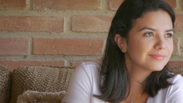 tag träumen. dolly nahaufnahme einer nachdenklich und entspannt hispanic junge frau sitzt auf einer couch im wohnzimmer zu hause - introspektion stock-videos und b-roll-filmmaterial