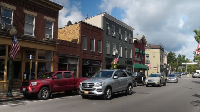Day Establishing Shot of Generic Small Town Main Street Storefronts A daytime exterior establishing shot of a generic small town's Main Street shopping district storefronts and traffic. Store marquees digitally removed for customization. americana stock videos & royalty-free footage