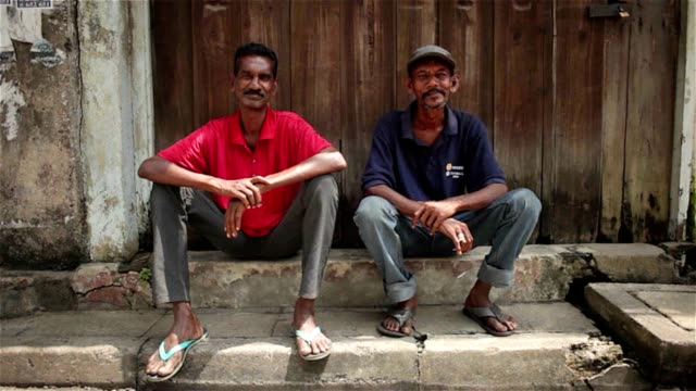A day in the life of Sri Lanka - men sitting on the street A day in the life of Sri Lanka - 2 men sitting on the street - smiling and happy colombo stock videos & royalty-free footage