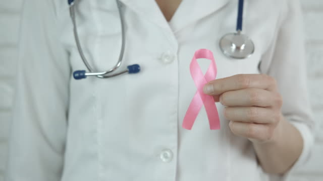 Day of breast cancer. Day of breast cancer. A doctor with pink awareness ribbon in her hand. A concept of breast cancer. breast cancer awareness stock videos & royalty-free footage