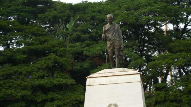 dag tid bangalore city famoius mahatma gandhi park staty slow motion 4k indien - india statue bildbanksvideor och videomaterial från bakom kulisserna