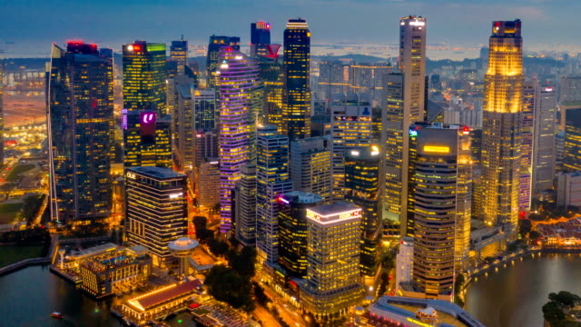 Day to Night Aerial view dronelapse or hyperlapse of financial central business district building of Singapore city