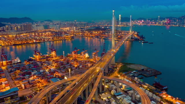 Day to Night Aerial view hyperlapse or timelapse of Hong Kong Kwai Tsing Container Terminals and Stonecutters bridge at dusk