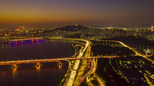 Day to night Hyperlapse or Dronelapse Aerial view of Seoul downtown city skyline with light trails on expressway and bridge cross over Han river at night in Seoul city, South Korea. Day to night Hyperlapse or Dronelapse Aerial view of Seoul downtown city skyline with light trails on expressway and bridge cross over Han river at night in Seoul city, South Korea. namsan seoul stock videos & royalty-free footage