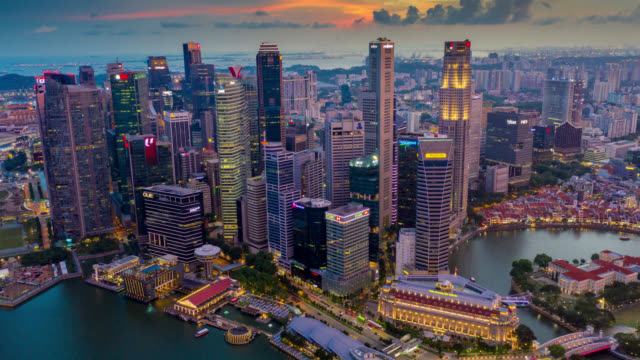 Day to night Hyperlapse or Dronelapse scene of Singapore business district downtown at sunset