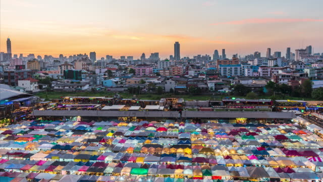 Day to night time lapse of Ratchada Train night market with beautiful sunset in Bangkok,Thailand.
