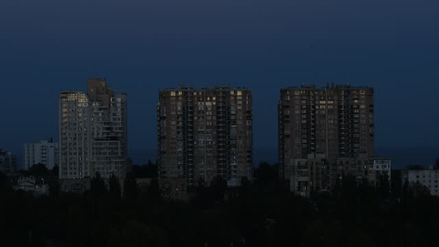 Day to night time lapse over urban skyline near waterfront Day to night transition timelapse of multistorey apartment buildings. European city with lights turning on in windows after getting dark. Fast paced city night-scape time lapse at urban seaside ocean front properties stock videos & royalty-free footage