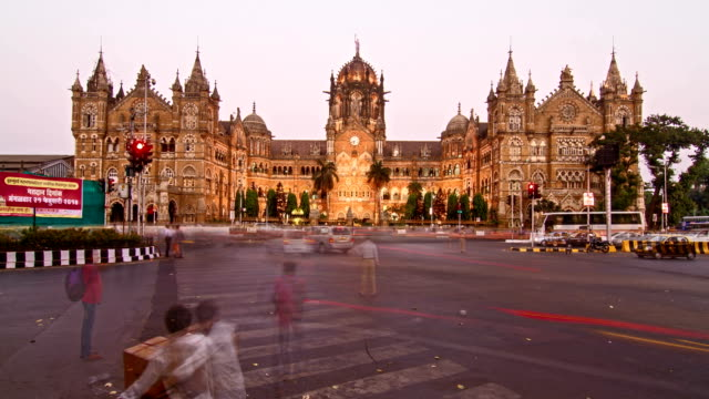 Day to night time lapse shot of traffic moving in front of Chhtrapati Shivaji Terminus (CST) formerly known as Victoria Terminus (VT) is being lit up as the night approaches, Mumbai, India video