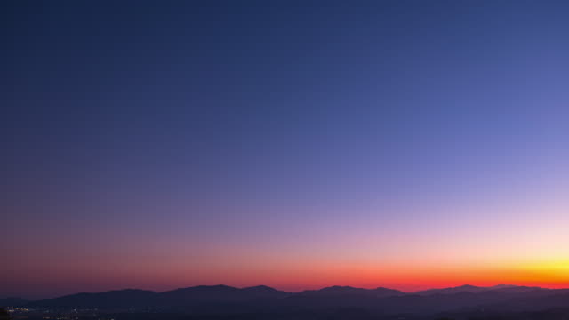 vídeos de stock, filmes e b-roll de day to night timelapse, beautiful orange e violet sunset dusk scene above the high mountain turning to the night scene with many stars. - pôr do sol