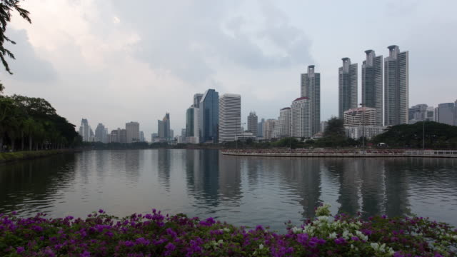 Day to Night Timelapse of Bangkok Condominiums and Business Towers Reflecting in Benjakitti Park Pond video