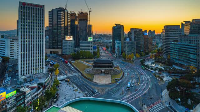 vídeos de stock, filmes e b-roll de do dia para a noite timelapse sungnyemun portão (mercado namdaemun) ou portão de namdaemun com trilhas leves de carro à noite em seul, coréia do sul. - coreia