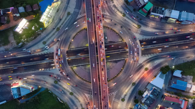 vídeos de stock, filmes e b-roll de dia a noite zoom em: tráfego rodoviário círculo com zoom in - entroncamento estrada