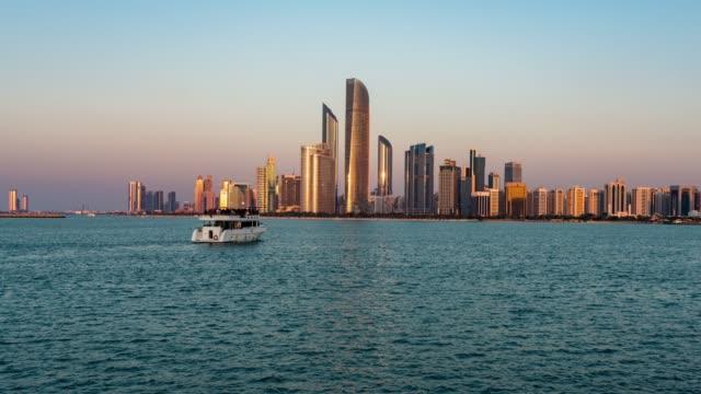 stockvideo's en b-roll-footage met dag tot nacht/time lapse de skyline van abu dhabi bij zonsondergang/abu dhabi, verenigde arabische emiraten - perzische golfstaten