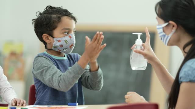 Video Daycare instructor providing hand sanitizer to child