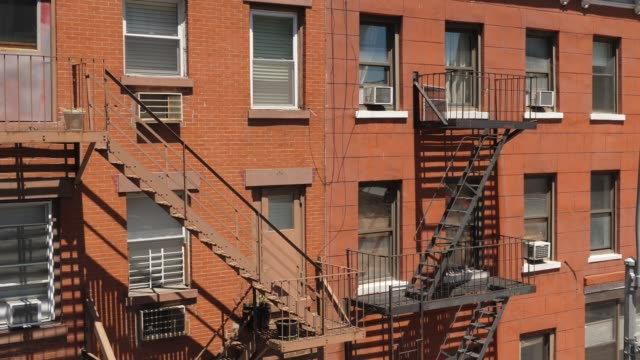 Daytime Exterior Establishing Shot of Typical Manhattan Apartment Building A daytime exterior establishing shot of a typical red brick apartment building with fire escapes along the side. house rental stock videos & royalty-free footage