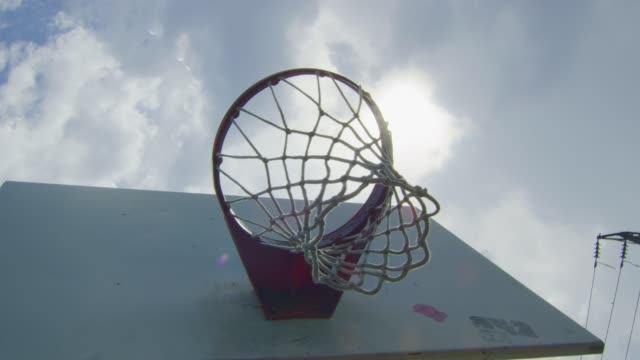 Daytime slow motion shot from underneath a basketball hoop video