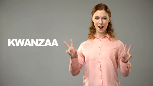 Deaf lady saying kwanzaa in sign language, text on background, communication video