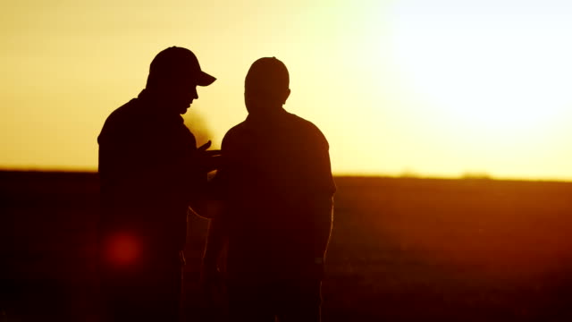 Deal in agribusiness. Two male farmer communicate on the field, use a tablet - shake hands. Silhouettes at sunset - vídeo