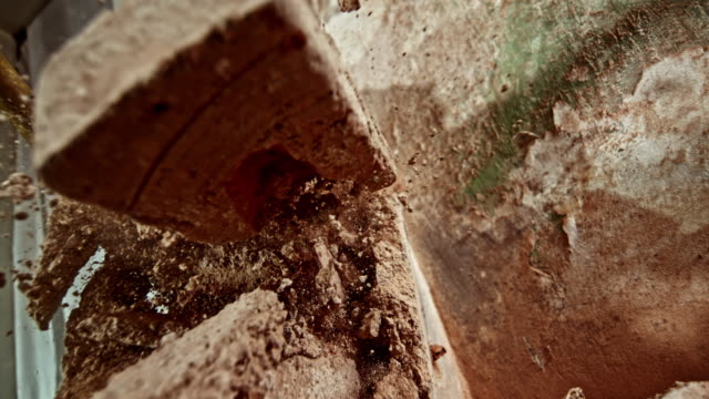 SLO MO Debris falling on the camera as the brick wall is struck with a sledge hammer