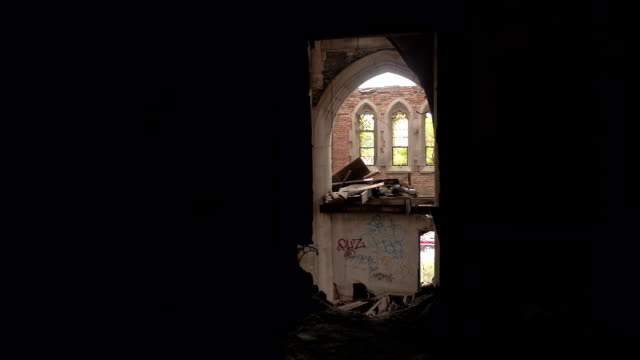 POV: Decaying old gothic cathedral as seen through a hole in a ruined brick wall video