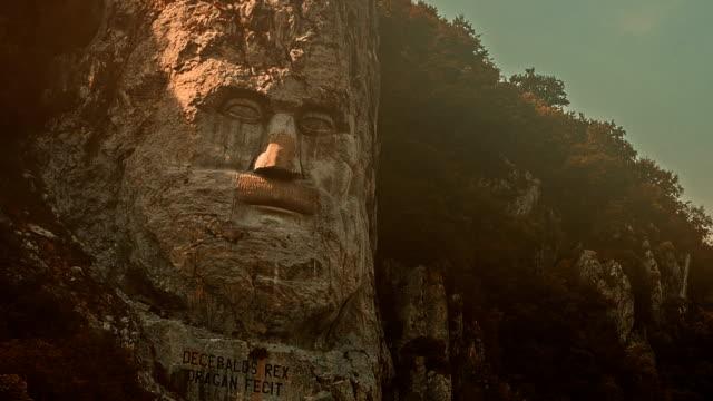 vídeos de stock e filmes b-roll de decebal paredão rochoso pôr-do-sol - dia de reis