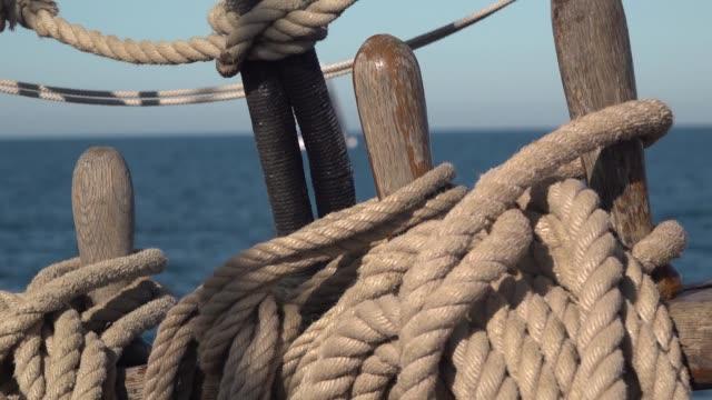 Deck organizer wish pin and the ropes of old sailing ship at sea. Slow motion video.