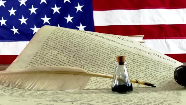 Declaration of Independence - USA American Declaration of Independence with modern American Flag in background.  Quill and antique ink bottle sitting on document. fourth of july videos stock videos & royalty-free footage