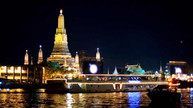 decorated boat in river behind Wat Arun, Bangkok, Thailand video