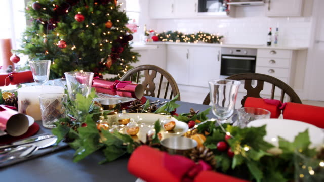 A decorated Christmas dinner table with Christmas crackers arranged on plates in a dining room, with a Christmas tree and kitchen in the background