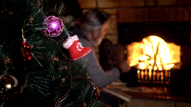 Decorated christmas tree with senior man near fireplace on the background Decorated christmas tree with senior man near fireplace on the background. A man throw woods into fire. firewood stock videos & royalty-free footage