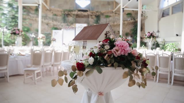 Decorated flowers with toy home as a symbol of good life for newlyweds. Wedding reception table in restaurant for bride and groom