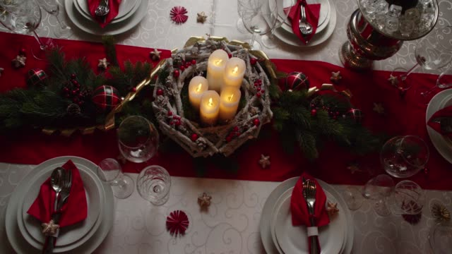 decorated table for christmas dinner with candles and christmas ornaments - christmas table video stock e b–roll