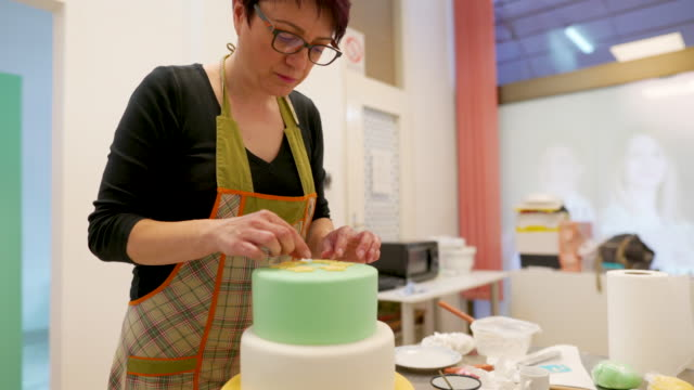 Decorating a cake Adult woman making a decoration for cakes in domestic kitchen pastry dough stock videos & royalty-free footage