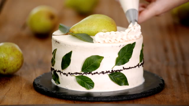 Decorating a cake with cream using piping bag. Woman confectioner makes chocolate cake with pear.