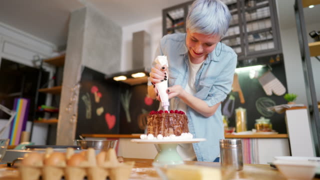 Decorating a cake with pleasure Young woman making a cake at her kitchen. blue hair stock videos & royalty-free footage