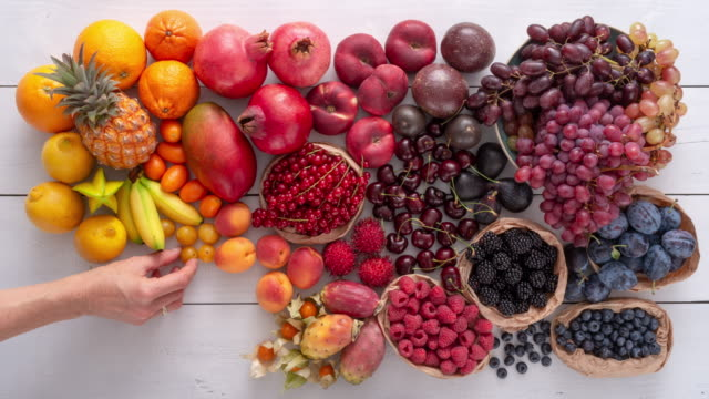 vídeos de stock e filmes b-roll de decorating a variety of colorful fruits on a white wooden table. colourful thanksgiving or harvest concept. - damasco fruta