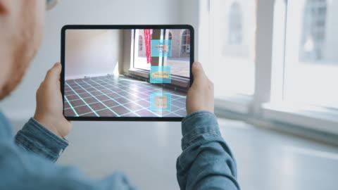 vidéos et rushes de appartement de décoration: man holding digital tablet avec ar interior design software choisit des meubles 3d pour la maison. homme pick sofa, table, lampe pour salon. sur l'écran d'épaule avec le rendu 3d - bureau ameublement