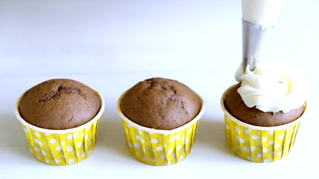 ホワイトクリームとチョコレートカップケーキを飾ります。調理袋を使用して、誕生日パーティーのためにマフィンを作る菓子。スローモーションでホームベーカリーのコンセプト。閉じる� - カップケーキ点の映像素材/bロール